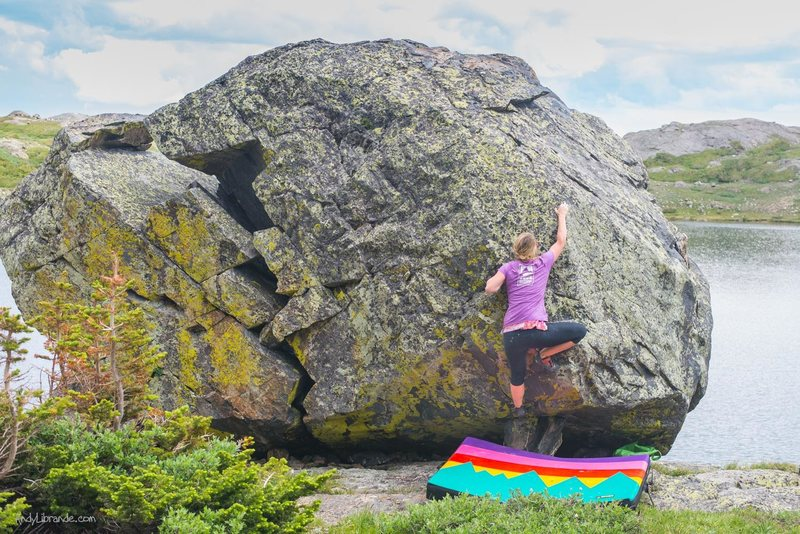 Incredible location! This boulder sits on top of a cliff over the lake.<br> <br> Only 1-3 climbs at most, the but location is quite impressive. <br> <br> Caitlin taking the 1st ascent after clearing a few holds of thick lichen. <br> <br> 4th of July, 2015.