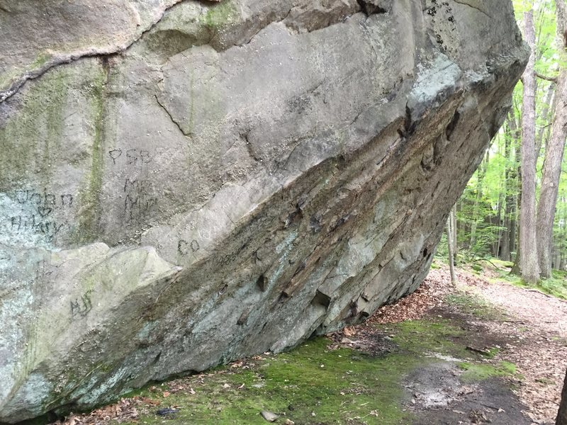 Larger boulder with at least 3 established problems on it including this overhanging traverse.