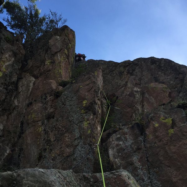 This is the start of pitch 2. If you go left where the climber is, you will hit another set of bolt anchors. If you go right up the V dihedral, you will be on sustained, runout 5.6 and almost at the top of the formation when you top out. Great view of leader from belay stance.