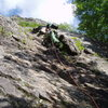"""Starting up P1 of """"Hogo's"""" - the bolts on the slab are hidden but are above and to the right of the climber"""