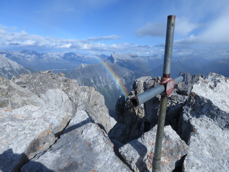 Summit cross on Mount Louis with Mount Rundle in the distance. A light storm brought a nice rainbow.