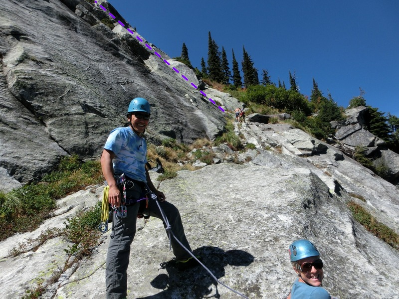"""Topping out on Have a Line to the """"start ledge"""" for most routes. The two climbers racking up in the background are at the base of the Harem route."""