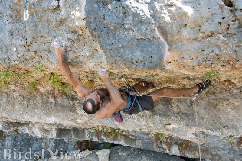 Rupesh sticking the first hold above the lip, prepping to toss for the next hold above. The crux