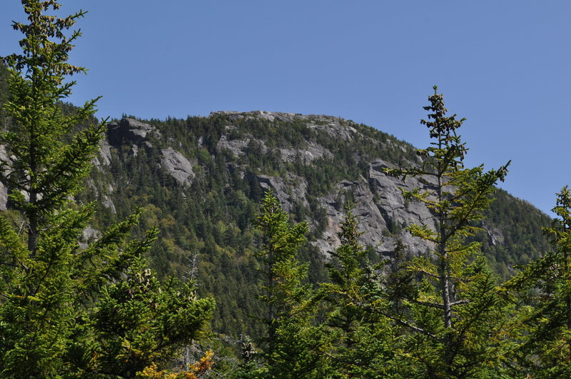 Tumbledown east peak crags (right) and Loop Trail/Fatman's misery exit (leftmost notch)