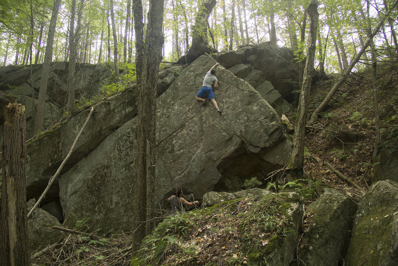 Ryan MacGlaflin topping out the boulder.