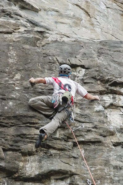 Climber working the crux of the 1st route on the far right of 5.13 Wall - Left Side