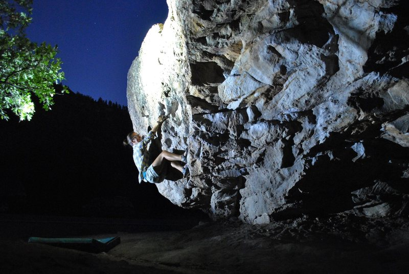 Leah getting on the roadside boulder at night.