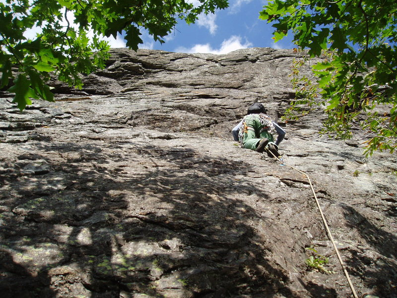 "P2 - Climbing on the ""black band"". Taking the ""right-hand choice"" above the ""ST"" ""engraved"" in the rock. Climber is about to start the traverse left."