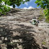 """P2 - Climbing on the """"black band"""". Taking the """"right-hand choice"""" above the """"ST"""" """"engraved"""" in the rock. Climber is about to start the traverse left."""
