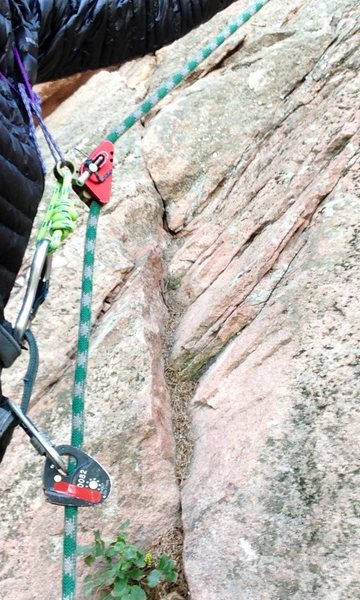 Top Rope Solo; toprope solo; tr solo<br> <br> Ditch the backup knots AND self belay hands free!  <br> <br> Use a fixed single rope.  (Backup lines are like gumby thongs to tr soloists in the know.)<br> <br> It is possible to use a variety of ascenders in the demostrated configuration.  Pictured are a microcender as primary (toothless mechanical prusik allows some slippage to reduce dynamic loads and can be moved down the rope easily with one hand).  Micro traxion as secondary (light, low friction).  <br> <br> Hold primary up with makeshift chest harness for zero slack.  Extend primary with full strength cord so that, in the event of failure or slippage of the primary, the secondary does not jam against the primary (lesson learned from experience and a mangled secondary).  <br> <br> The extension on the primary also aids in transitioning to a descending device https://www.mountainproject.com/v/112146813<br> <br> TR solo only!  Do not try to rope solo (i.e. lead) with this setup!