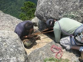 Teaching a local how to set up an anchor on a giant boulder.
