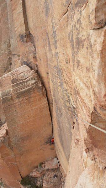 Tim climbing off-width portion of pendulum pitch.
