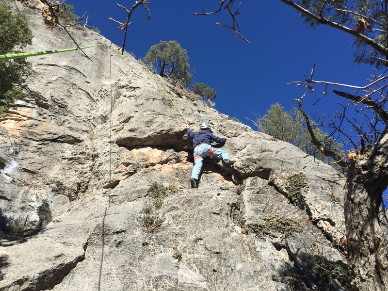 Climbing through the roof at the lower crux of The Harvey.