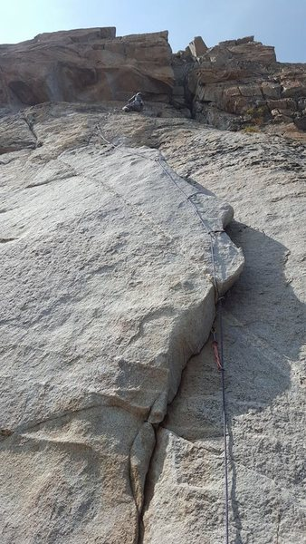 awesome alpine flake to a finger tips crack. about 80ft.. (crack looked way bigger from the base..had to aid through it.. a fall would of sent you onto the ledge atop the flake.) 5.8 A0. FA: labor day weekend.