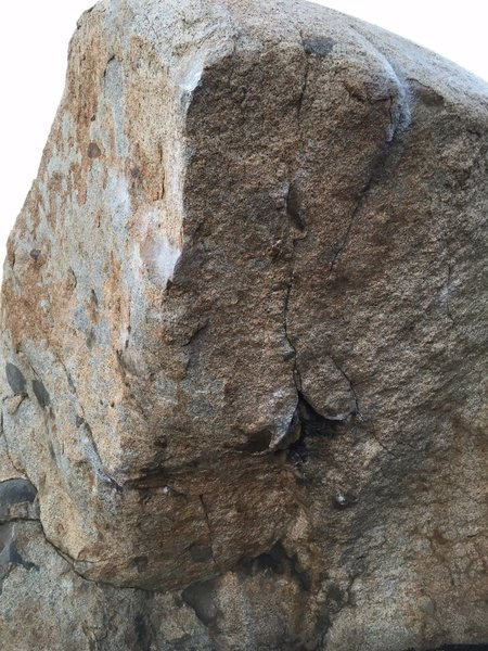 Start both hands around same height (right is at bottom of upside down V at base of crack down center of face). Work left hand up arete to razor sharp edge. Used crappy right heel to get crimp out right, befor big move to top of right arete. Come into flaring crack up top and mantle with difficulty.
