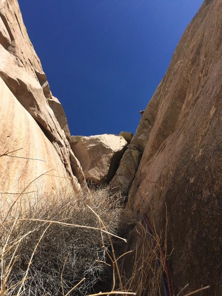 A large chockstone in a narrow section of the Long/Broken Ribs gully can be turned on the right in order to reach the large south wall of middle section of Broken Rib. The route (5.7?) is marked by the ropes in the photo, and Ian Harris can be seen above.