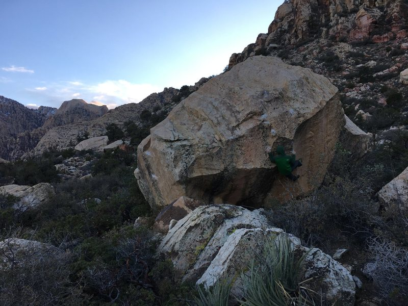 The east face. The Sugar Baby boulder is obscured and lies directly to the west. The climber is on Dance Magic Dance.