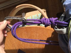 Tied correctly through a harness and finished with a locking carabiner.