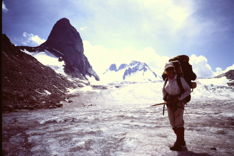 Mary-Jane Cross packing from Kain-Camp (aka &quot;Boulder Camp&quot;) to the ACC-GMC Vowell-camp via the Snowpatch- Bugaboo col and the Vowell Glacier (1982).<br>  Bugaboo on the left, Howser Towers in background.