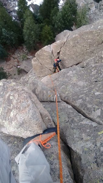 Finishing the second pitch. Note and beware of the huge detached flake behind my belayer.