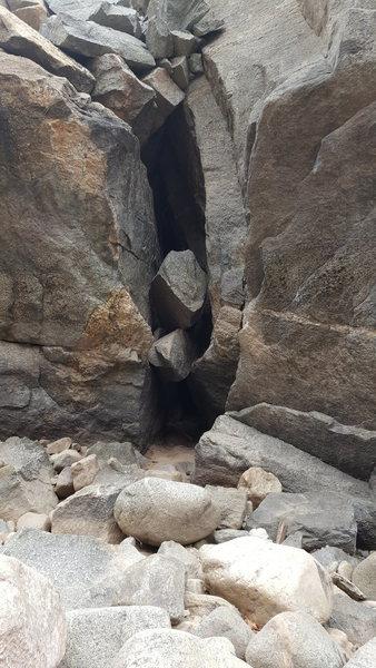 Climb the right arete of the left boulder, follow?