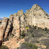 View from the south summit and looking at true summit and Kinesava with arrow pointing to location of petroglyph panel.