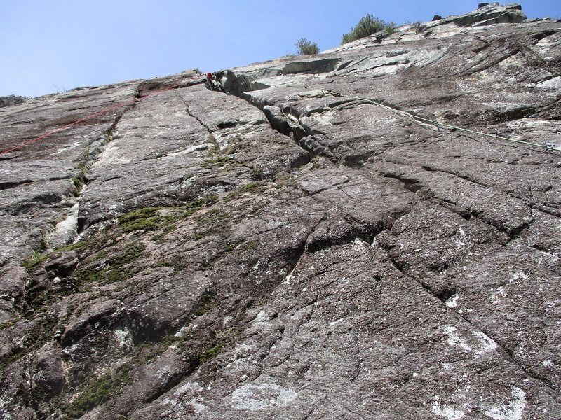 Looking up Lovin' Arms from the top of Davis Holland. Pitch 1 leaves the ledge on the right, goes up a tricky crack, and then up the chimney to a pair of bolts on the left wall of the chimney.