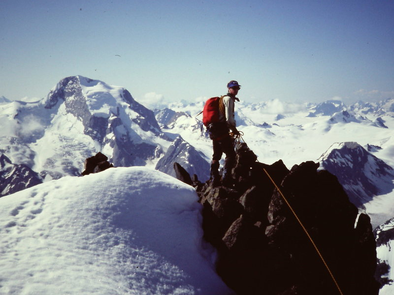 [Photo#10] Steve Latham on the summit (of East Peak or of Pioneer ??) with Mt Sir Sandford in the background