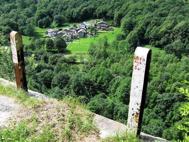Looking at the village of Vho from the old highway at the Vho crag.  Route names marked on the posts at the top of the below sector.