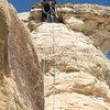 Easing over the caprock. Runout but fun free climbing.