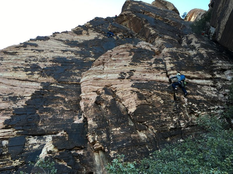 Three climbers simulclimbing pitch 3, outlines the  route, starting from crack near right end of terrace, in the route description.