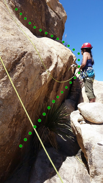 Climber negotiating the clunky gap at the start of the route.  One alternative is to walk onto the ledge from the right with a little bit of angling arete in the beginning