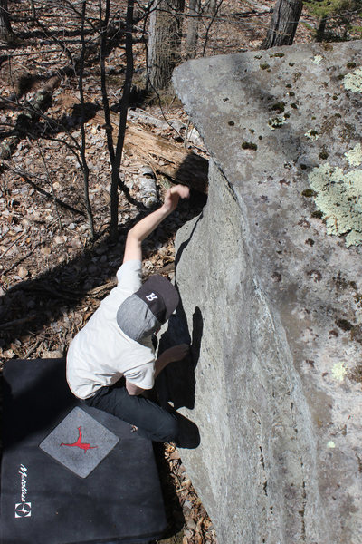 Harry making the big reach up the arete from the sit start.