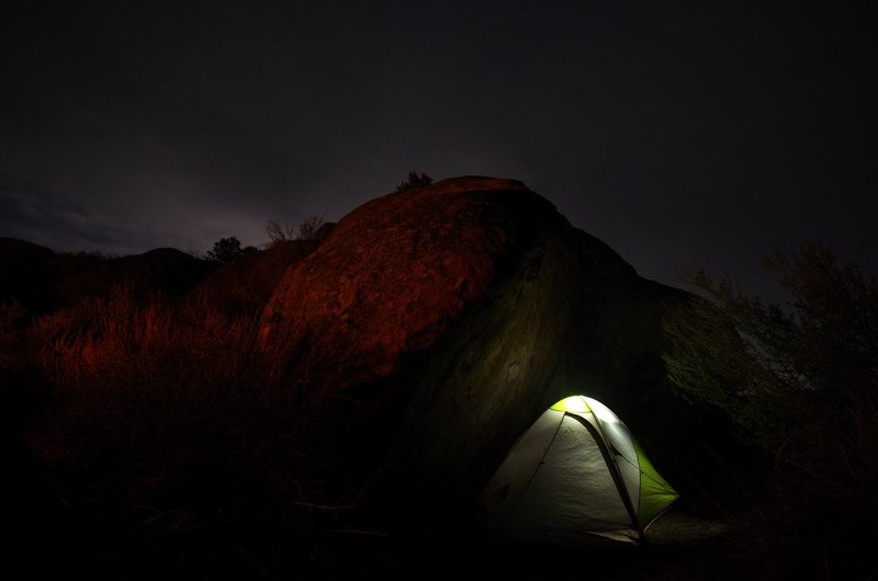Campsite under boulder at night.