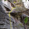 The base of the route and the start of the first pitch. Begin by climbing the chimney behind the rectangular block in the foreground (dotted line) and continue to belay in a corner under the roof (approximate position of the belay is marked)