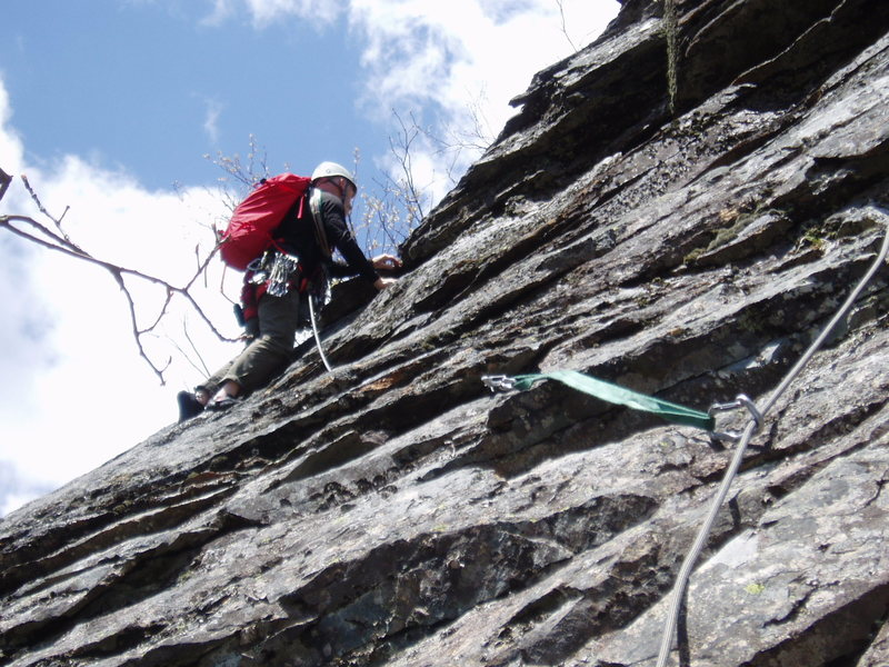 """JS at the """"nose"""" at the end of the traverse on P2. Climber has taken the """"left-hand choice"""" to the bolt, which is not seen but is the clip above the sling."""