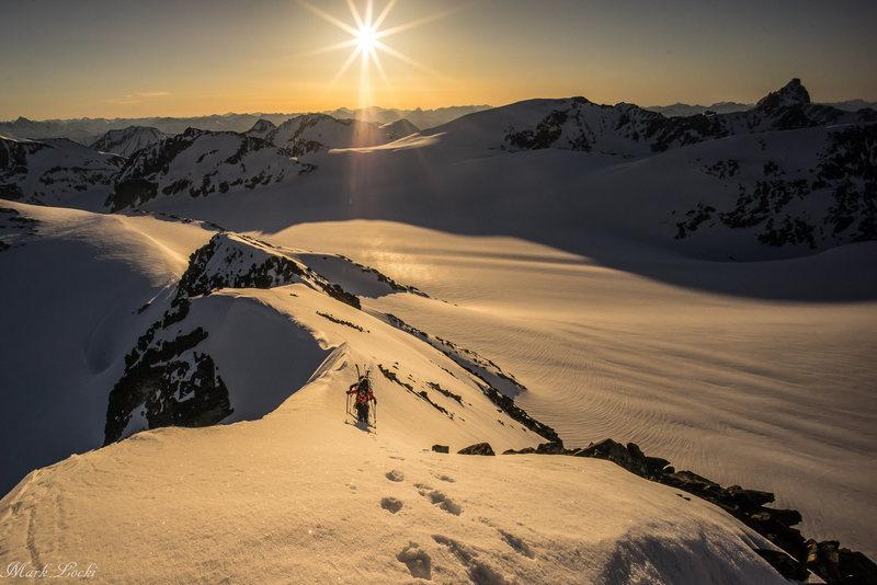 2 climbers moving along the ridge as the sun rises