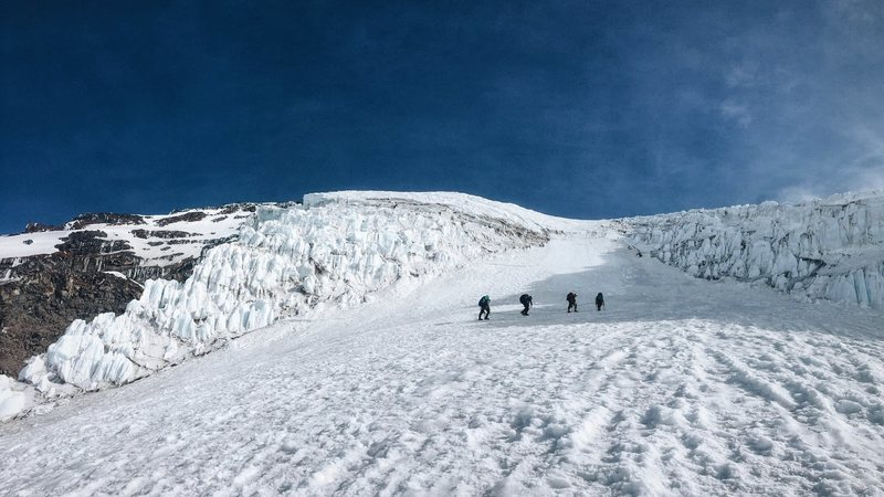 An Alpine Ascents International climbing team approaching the upper ice chute of the Kautz Glacier.