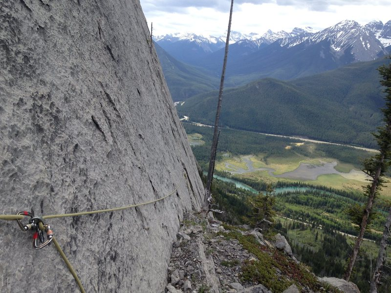 Belay ledge at the top of pitch 4. The right hand belay option is in front of the dead tree