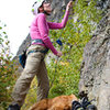 """Trish belaying on """"E"""" with her tired puppy at her feet. Photo Credit: Darryl Han"""