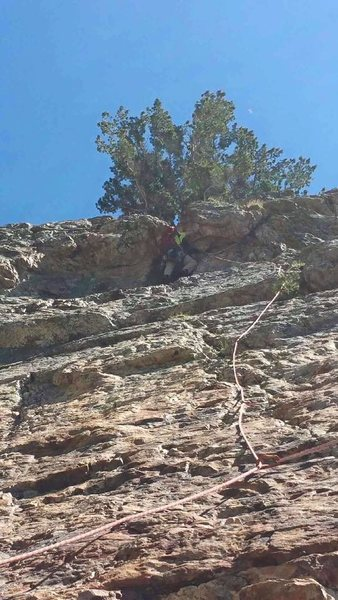Garon cruxing the 5.10a roof on the first pitch with his 60 L pack on.