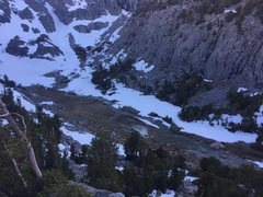 Sam Mack in the evening during the descent. The tent pad is dry enough to camp, but it's wet/snowy all around.