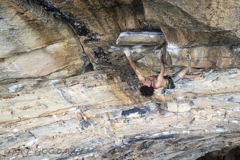 """Kevin Umbel digging into the Corner Pocket (13a) at First Buttress in the Meadow River Gorge, WV. Also in the pic is Anthony Love climbing on Black Crack (12c), a seldom repeated trad climb first freed, onsite, by Peter Croft in 97; Doug Reed had the route cleaned up and ready to go, but a sneaky local told Peter it was no biggie, only to back peddle after the send, suggesting to Peter that he """"leave the area, post haste""""! Although Black Crack is now afloat in a sea of bolts and fixed draws, it's still a proud tick for the area and by reputation, a bit harder than the neighboring 5.13 sport rigs."""