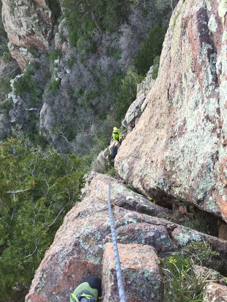 looking down at the belay at the top of p1 from a ledge/block on p2