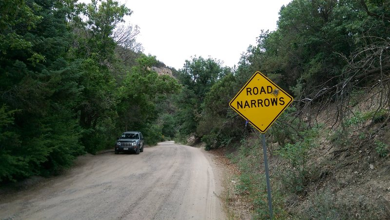 "View of the parking area and the ""road narrows sign"""