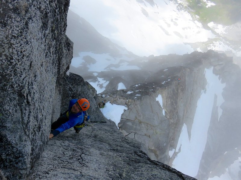 Climber leading Pitch 1 of the Gendarme, with the North Ridge stretching below.
