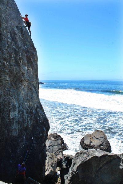 Nick closing in on the anchors as waves crash beneath him. True West Coast climb.