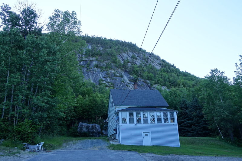 The approach trail (left of the boulder) and the cliff in the background.