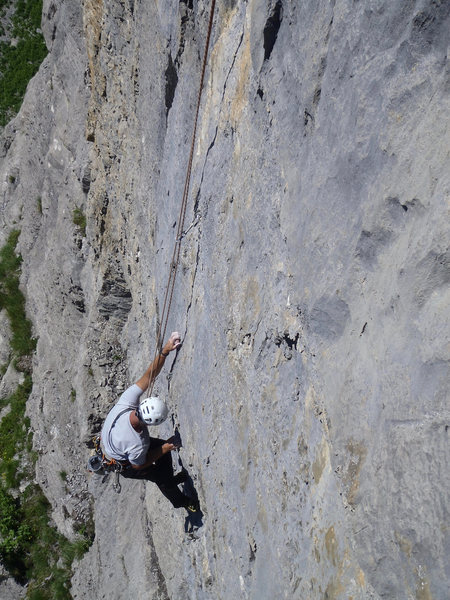 Left hand gripping the &quot@SEMICOLON@Rotpunkt&quot@SEMICOLON@ plastic hold, bolted to make this pitch only 6b. <br> <br> Not typical of this area, but just an extreme manifestation of facilitating &@POUND@39@SEMICOLON@plaisir&@POUND@39@SEMICOLON@ climbing in Switzerland!