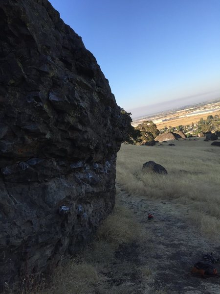 Side view of Boulder of bloody madness with stonewall in the back round.